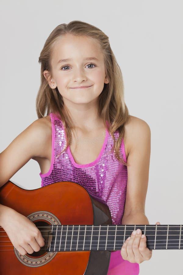 Porträt des jungen Mädchens Gitarre gegen grauen Hintergrund spielend lizenzfreie stockfotos