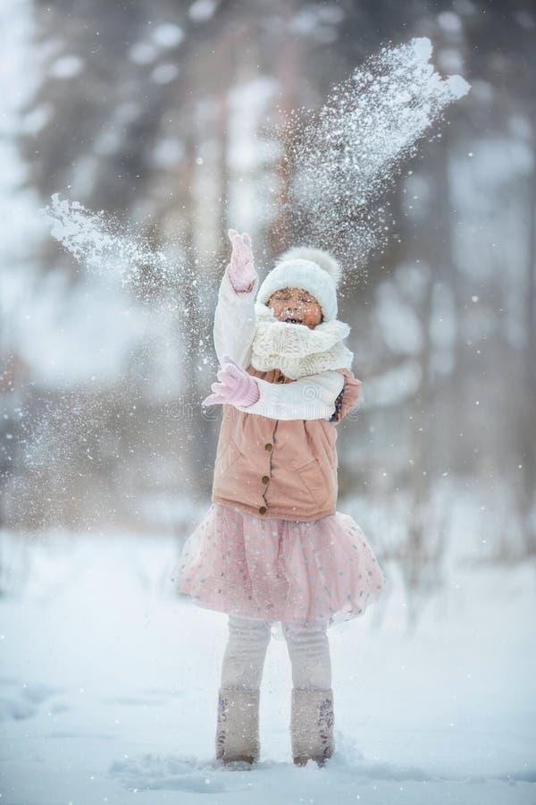 Porträt des jungen Mädchens haben Spaß mit Schnee im Winterpark stockfotografie