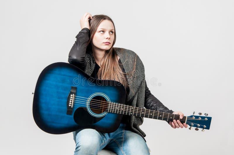 Porträt des jungen Mädchens mit blauer Gitarre lizenzfreie stockfotos
