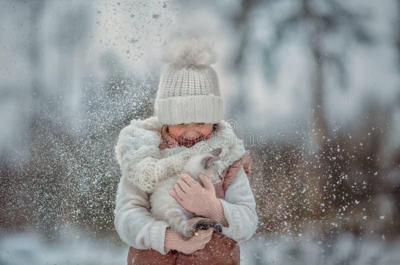 Porträt des jungen Mädchens mit Kätzchen unter Schnee lizenzfreie stockbilder