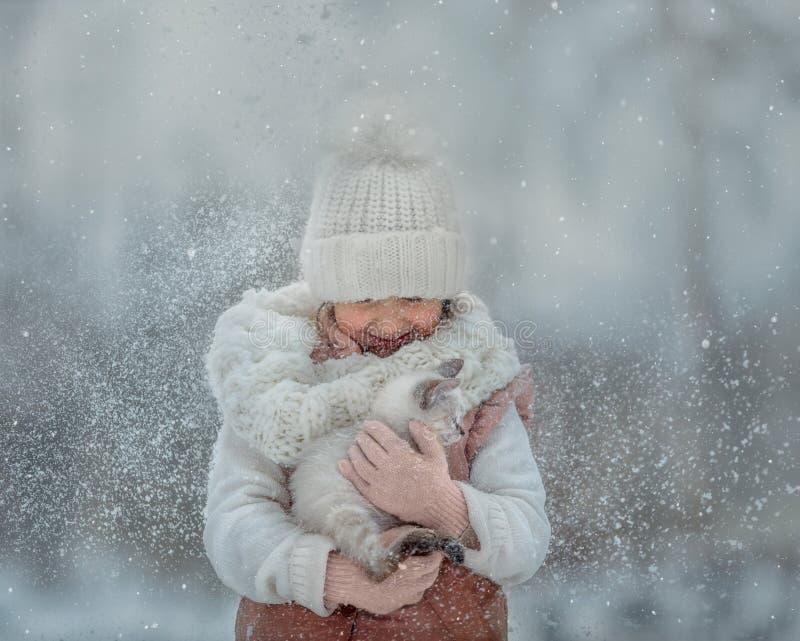 Porträt des jungen Mädchens mit Kätzchen unter Schnee lizenzfreies stockfoto