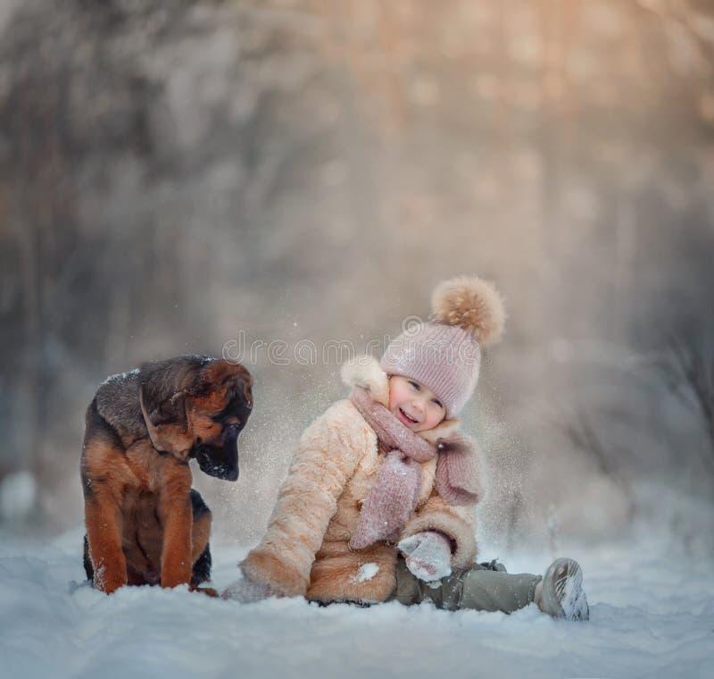 Porträt des jungen Mädchens mit Welpen unter Schnee lizenzfreie stockfotos