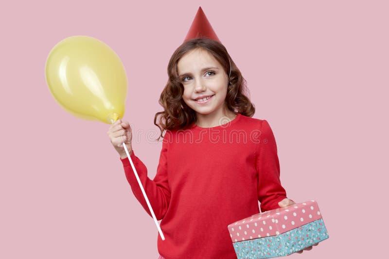 Porträt des jungen Mädchens schauend oben lokalisiert auf rosa Hintergrund In den Händen eines weiblichen Kindes war ein Geschenk lizenzfreie stockfotos