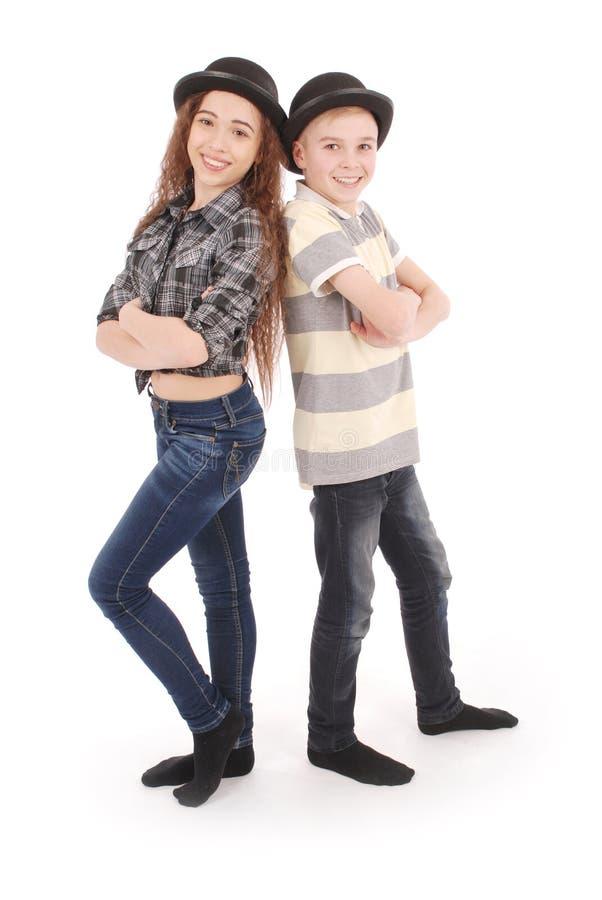 Porträt des jungen Mädchens und des Jungen, die in der schwarzen Melone aufwirft stockfotografie