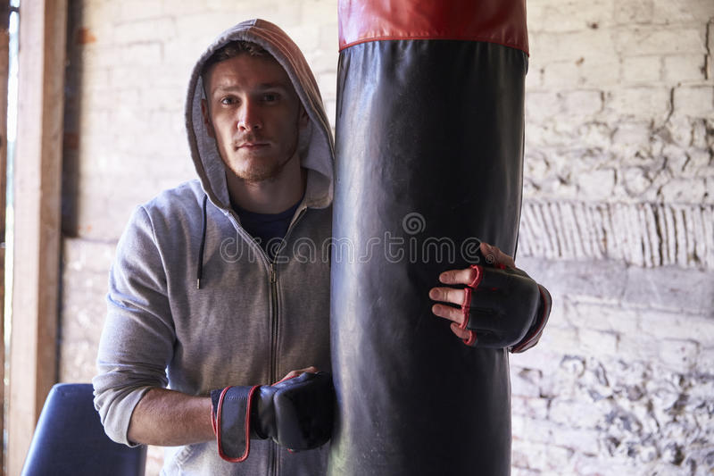 Porträt des jungen männlichen Boxers mit Sandsack in der Turnhalle lizenzfreies stockfoto