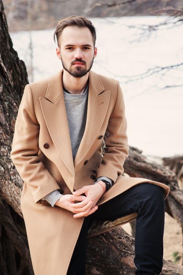 Porträt des jungen Mannes auf dem Weg im Herbstwald im beige Mantel lizenzfreie stockbilder