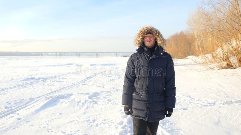 Porträt des jungen Mannes das Schauen in die Kamera am sonnigen Tag des Winters draußen einfrierend stockfotografie