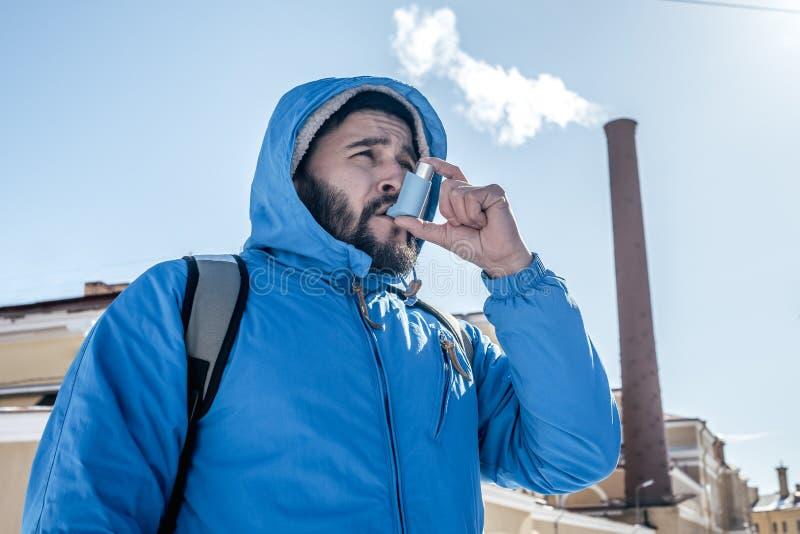 Porträt des jungen Mannes, der den Asthmainhalator im Freien verwendet lizenzfreies stockfoto