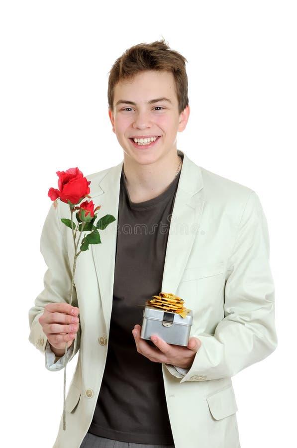 Porträt des jungen Mannes die Rose und das Geschenk über dem weißen Hintergrund anhalten stockfotos