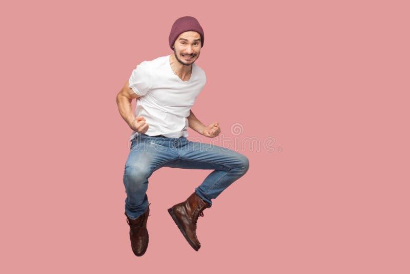Porträt des jungen Mannes des glücklichen bärtigen Hippies im weißen Hemd und in den Blue Jeans mit dem Hut, der seinen Sieg spri stockfotografie