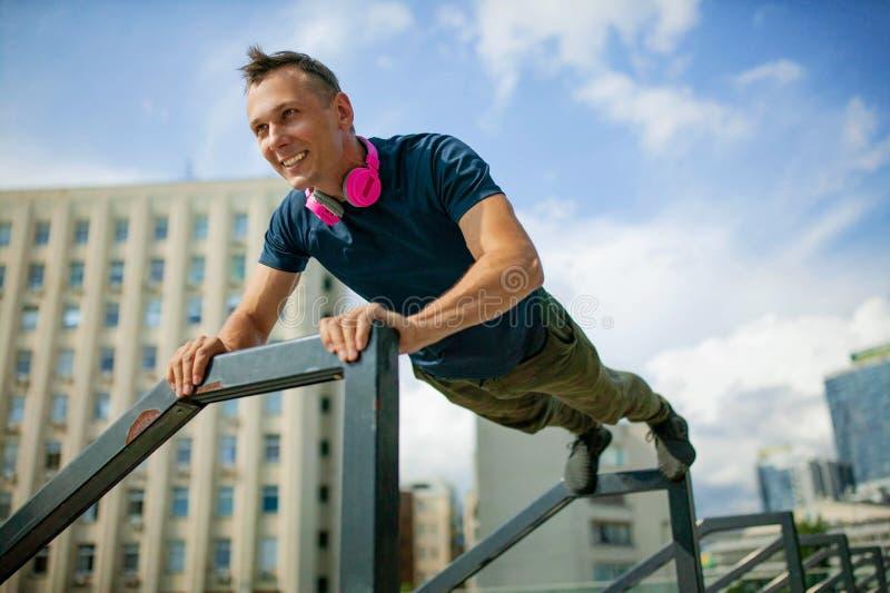 Porträt des jungen Mannes körperliche Bewegung auf Sportplatz tuend stockbilder
