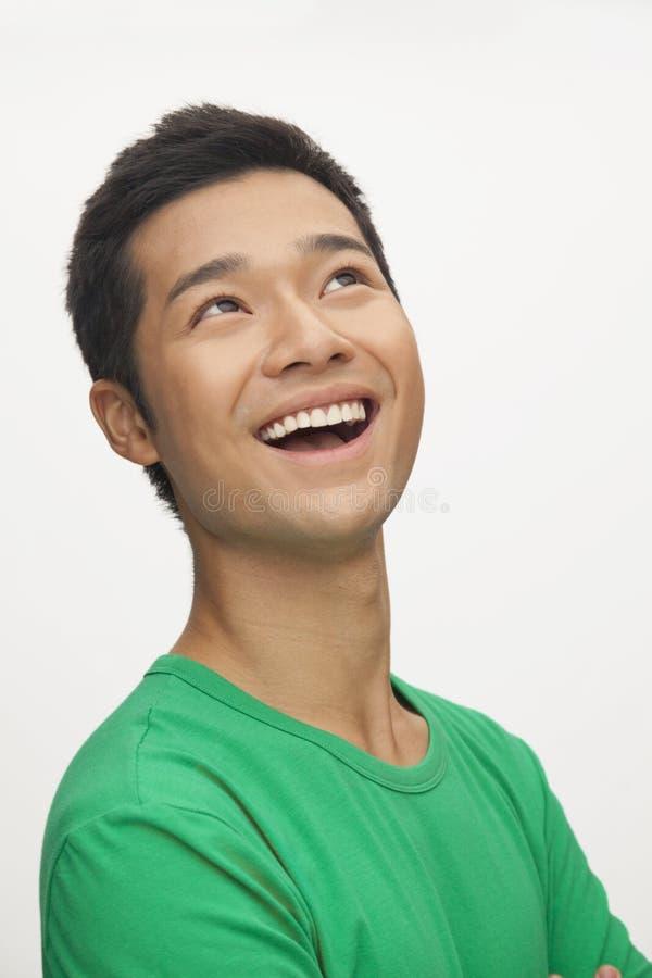 Porträt des jungen Mannes lächelnd in einem grünen Hemd, weißer Hintergrund stockbilder