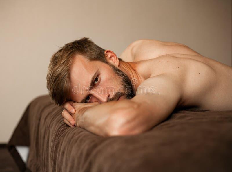 Porträt des jungen Mannes liegend auf dem Bett schulterfrei stockbilder