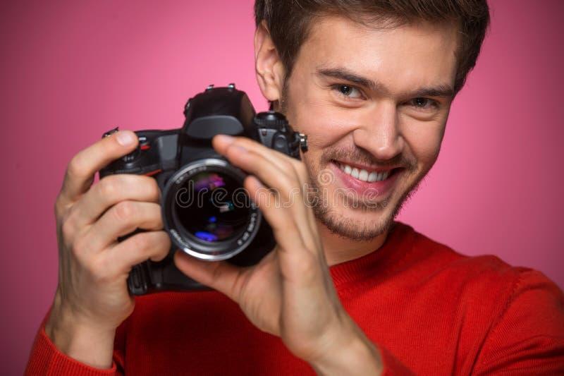 Porträt des jungen Mannes mit Berufsdigitalkamera stockfotografie