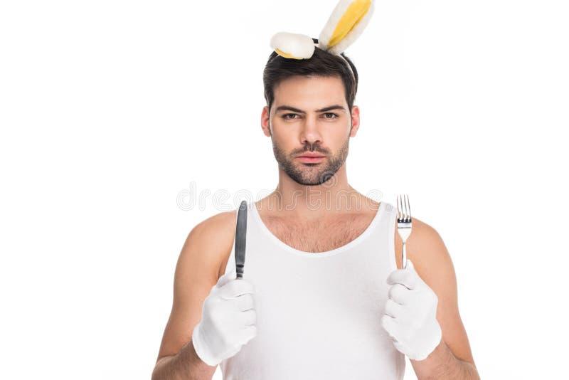 Porträt des jungen Mannes mit den Häschenohren, die Gabel mit Messer halten stockfotografie