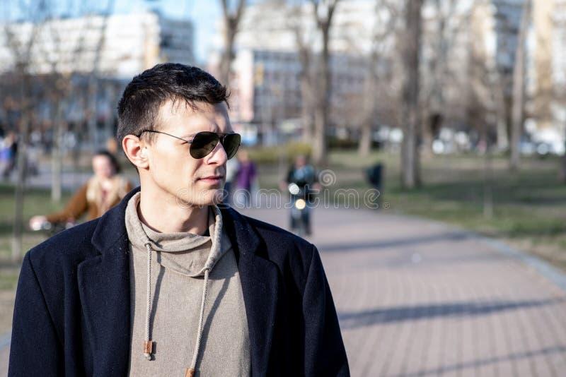 Porträt des jungen Mannes mit der Sonnenbrille und schwarzem Mantel im Freien im Park stockfoto