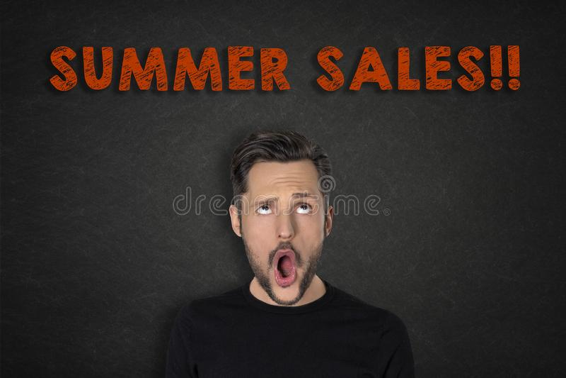 Porträt des jungen Mannes mit einem wow Ausdruck und 'Sommerschlussverkäufen!!! 'Text lizenzfreies stockbild
