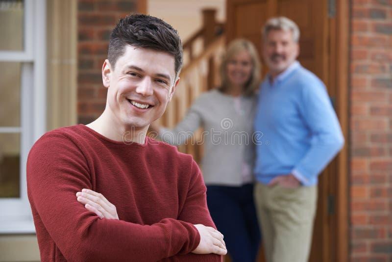 Porträt des jungen Mannes mit Eltern zu Hause stockfotos