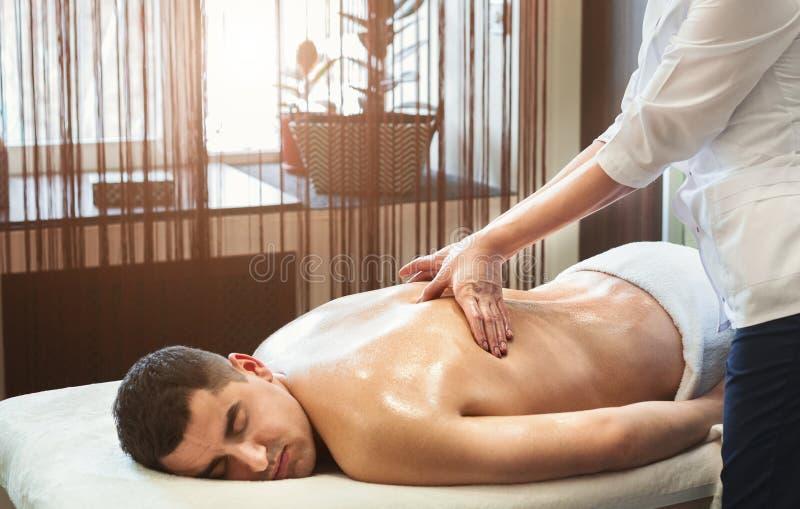 Porträt des jungen Mannes Rückenmassage empfangend lizenzfreie stockbilder