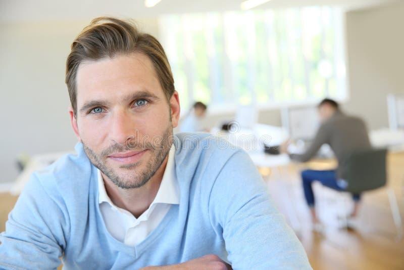 Porträt des jungen Mannes sitzend im Büro lizenzfreie stockbilder