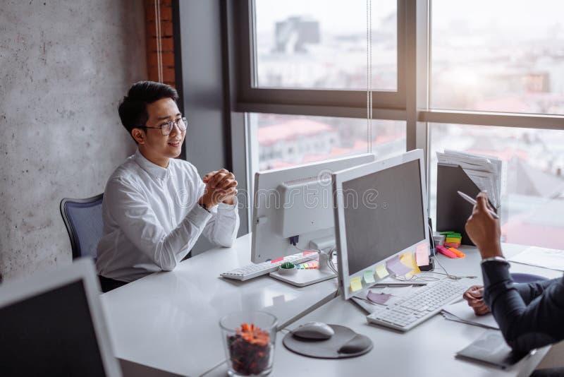 Porträt des jungen Mannes sitzend an seinem Schreibtisch im Büro lizenzfreies stockfoto
