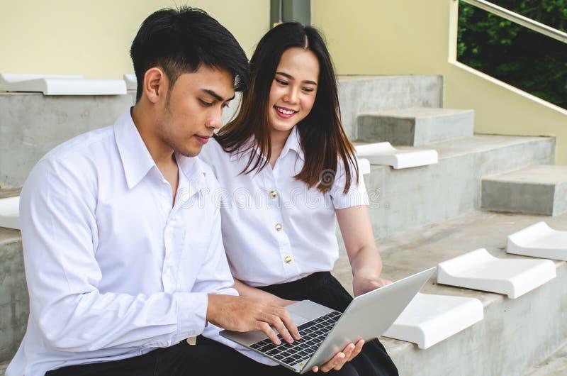 Porträt des jungen Mannes und des Mädchens in der Hochschuluniform, die an Laptop sitzt und arbeitet stockfotografie
