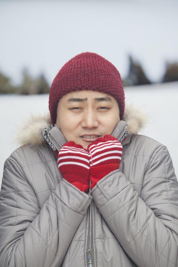 Porträt des jungen Mannes zitternd in der kalten Temperatur im Großen Mantel lizenzfreie stockfotos