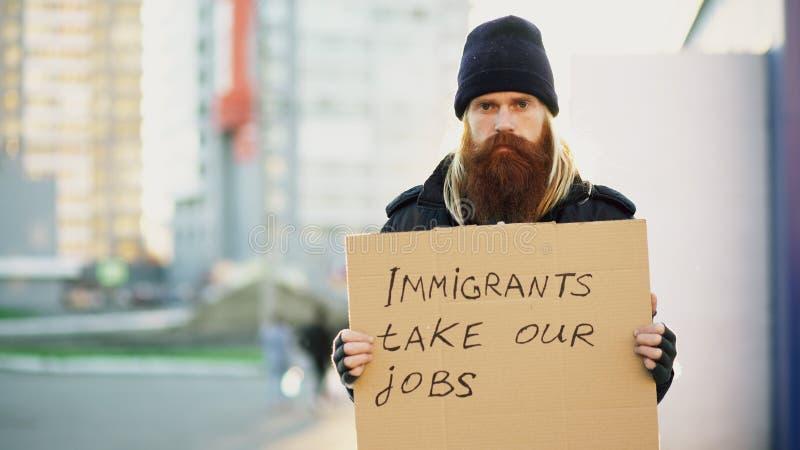 Porträt des jungen obdachlosen Mannes mit der Pappe, die Kamera betrachtet und sehr umgekipptes wegen der Immigrantkrise in Europ lizenzfreie stockfotografie