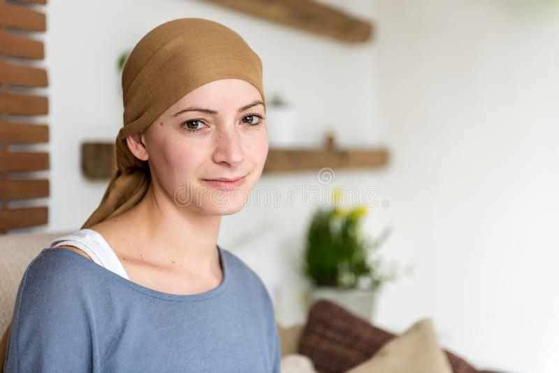 Porträt des jungen positiven Krebspatienten der erwachsenen Frau, der im Wohnzimmer, lächelnd sitzt stockfotos