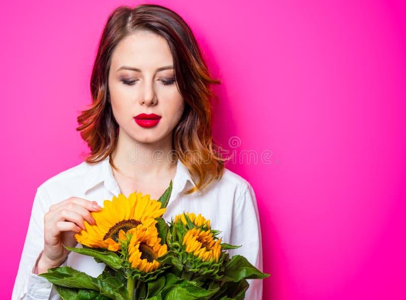 Porträt des jungen rothaarigen Mädchens mit Sonnenblumen lizenzfreie stockfotografie