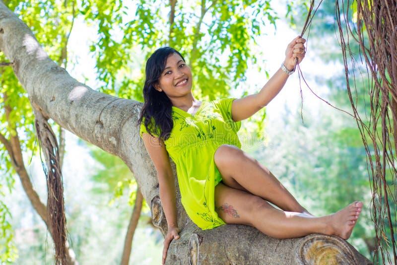 Porträt des jungen schönen asiatischen Mädchens, das am Banyanbaum lächelt an der Kamera sitzt lizenzfreie stockfotos