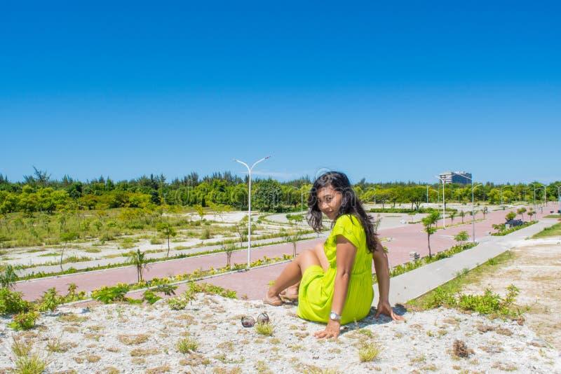 Porträt des jungen schönen asiatischen Mädchens, das an der Spitze des Hügels gegenüberstellt Kamera sitzt lizenzfreie stockfotos