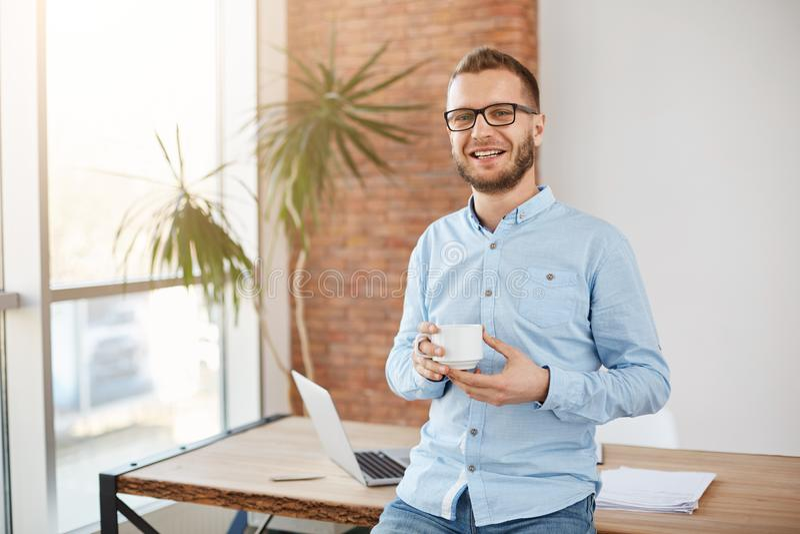 Porträt des jungen schönen bärtigen Unternehmers in den Gläsern und in der zufälligen Kleidung, stehend im hellen coworking Büro stockfotografie