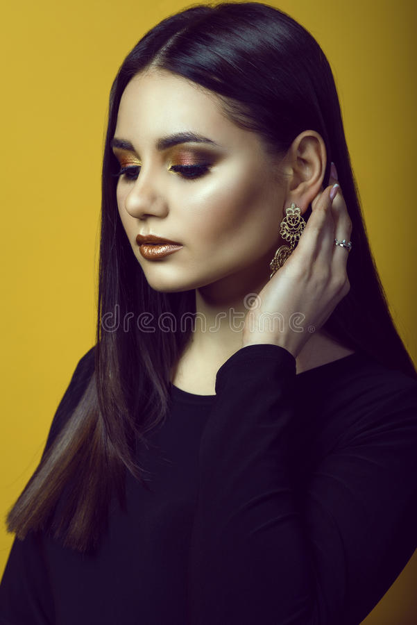 Porträt des jungen schönen dunkelhaarigen Mädchens mit Berufsmake-up in den goldenen und kupfernen Farben, die ihr Haar hinter de lizenzfreies stockfoto