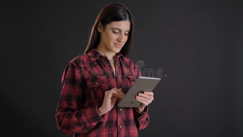 Porträt des jungen schönen langhaarigen Mädchens in plaided Hemd aufmerksam aufpassend in ihre Tablette auf schwarzem Hintergrund stockfotos