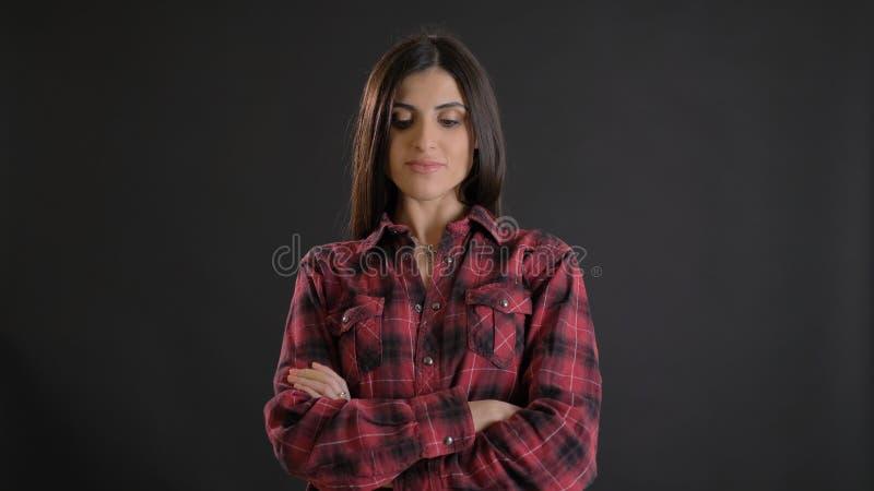 Porträt des jungen schönen langhaarigen Mädchens in plaided Hemd mit den gekreuzten Armen aufpassend froh abwärts auf Schwarzes lizenzfreie stockbilder