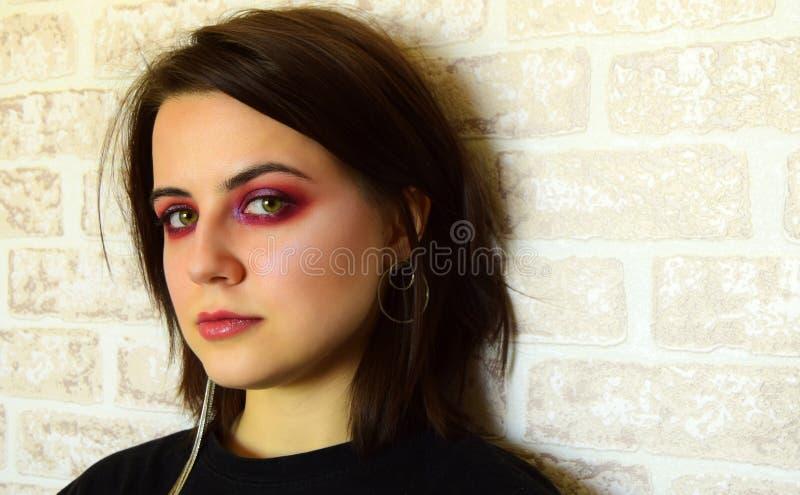 Porträt des jungen schönen Mädchens mit grünen Augen und ein helles kreatives Make-up in den lila Tönen lizenzfreie stockbilder