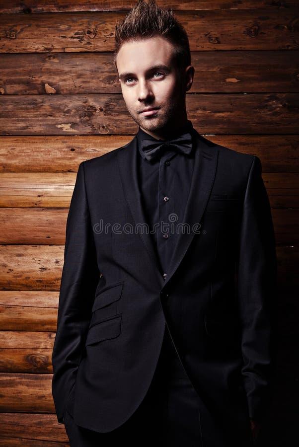 Porträt des jungen schönen modernen Mannes gegen hölzerne Wand. stockfoto
