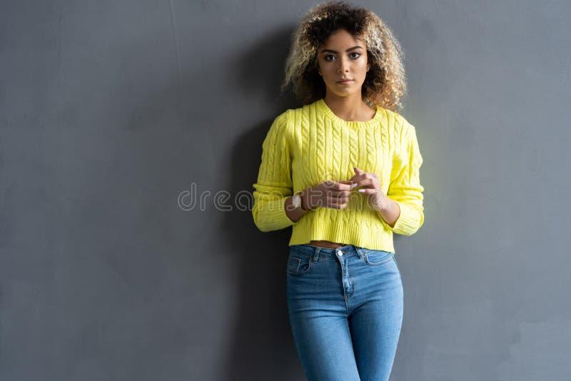 Porträt des jungen schönen netten netten schwarzen Mädchens, das Kamera über grauem Hintergrund betrachtend lächelt stockfotografie
