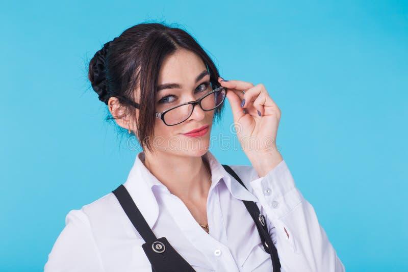 Porträt des jungen schönen netten netten Studentenmädchens mit Gläsern lächelnd, Kamera über blauem Hintergrund betrachtend lizenzfreies stockfoto
