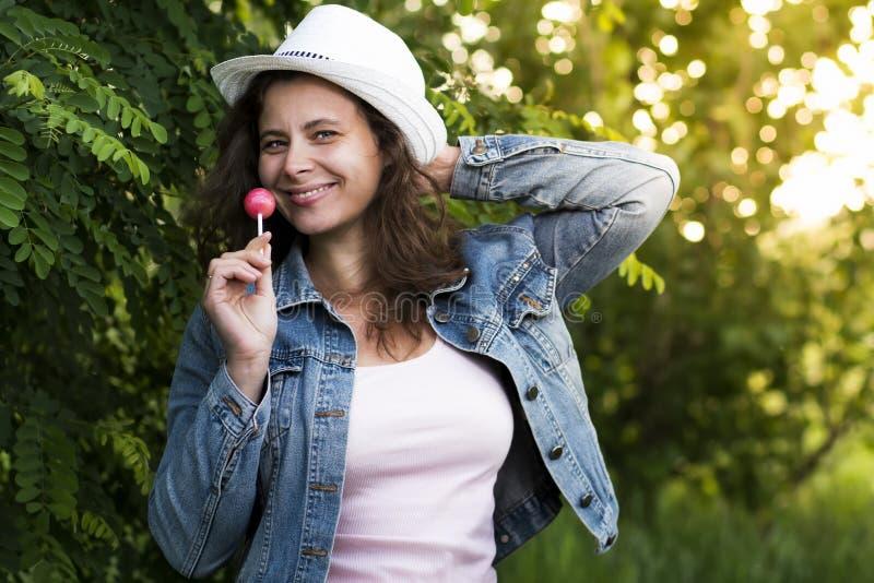 Porträt des jungen schönen stilvollen Mädchens im Hut mit süßen Karamellsüßigkeit chupa chups auf Stock auf Naturhintergrund stockbilder