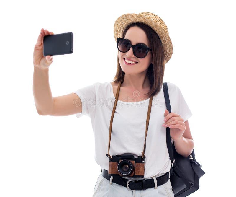 Porträt des jungen Schönheitstouristen im Strohhut, der selfie Foto mit dem Smartphone lokalisiert auf Weiß macht stockbild