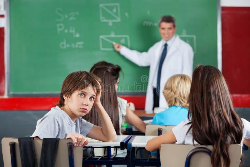 Porträt des jungen Schülers lehnend am Schreibtisch lizenzfreies stockbild