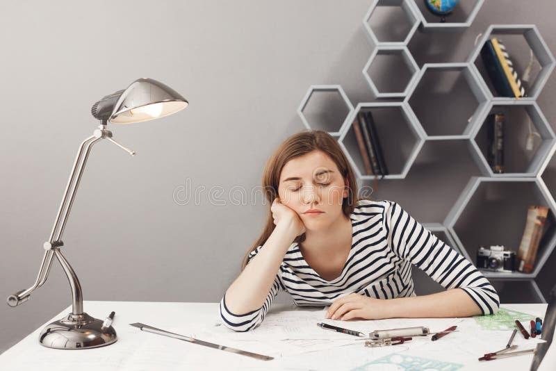 Porträt des jungen schläfrigen schönen weiblichen Designers mit dem dunklen Haar im gestreiften Hemd halten Haupt mit der Hand, f stockfotos