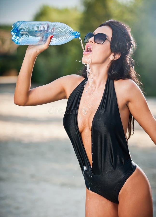Porträt des jungen sexy Brunettemädchens in Trinkwasser des schwarzen tief ausgeschnittenen Badeanzugs von einer Flasche Sinnlich stockfoto