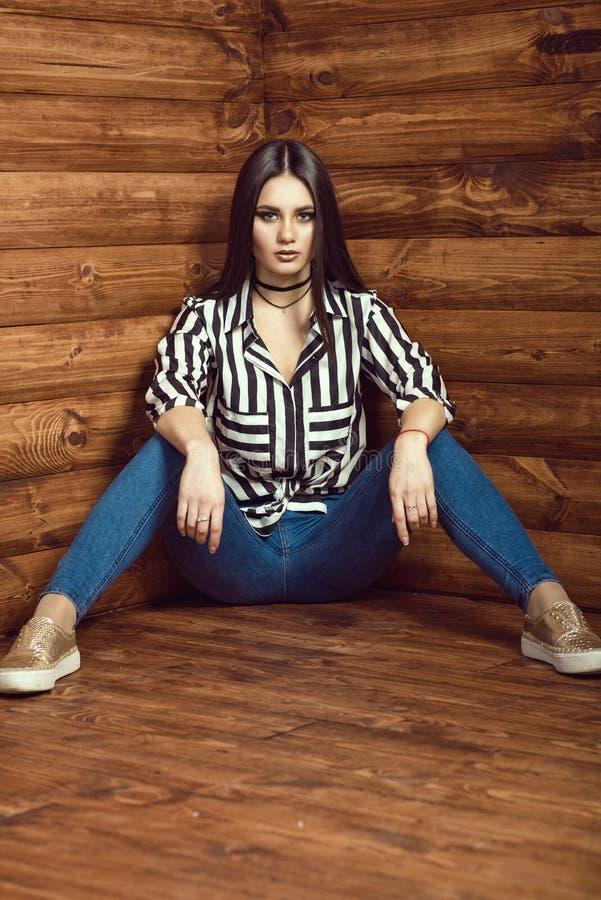 Porträt des jungen sexy dunkelhaarigen Modells, das dünne hoch-taillierte Jeans, gestreiftes gebundenes oben Hemd, Halsband und g stockfotos