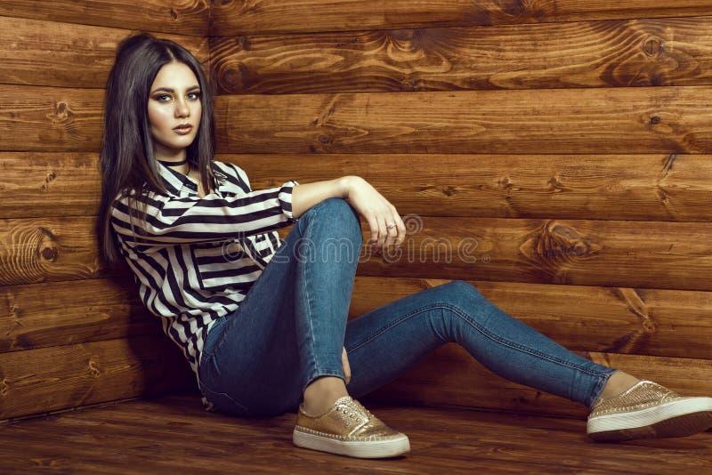 Porträt des jungen sexy dunkelhaarigen Modells, das dünne hoch-taillierte Jeans, gestreiftes gebundenes oben Hemd, Halsband und g lizenzfreies stockfoto