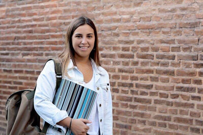 Porträt des jungen Studentenmädchens auf Backsteinmauer lizenzfreies stockbild
