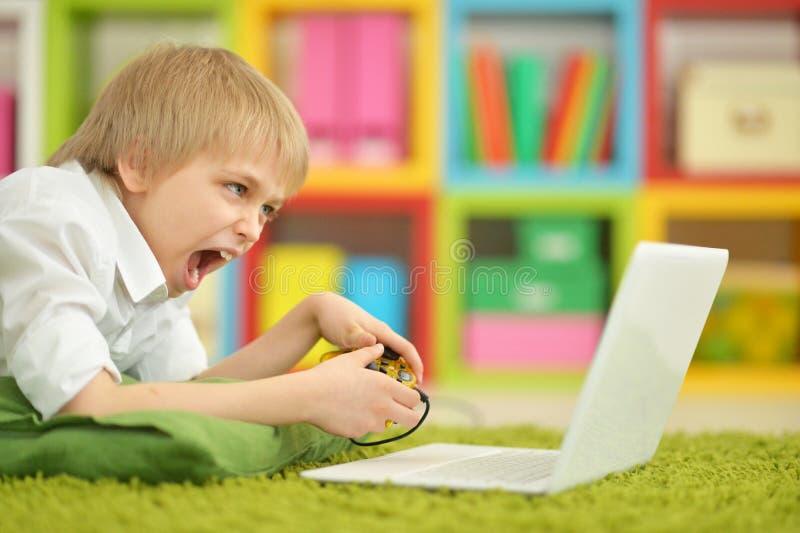 Porträt des Jungen Videospiel auf Laptop spielend stockfotografie