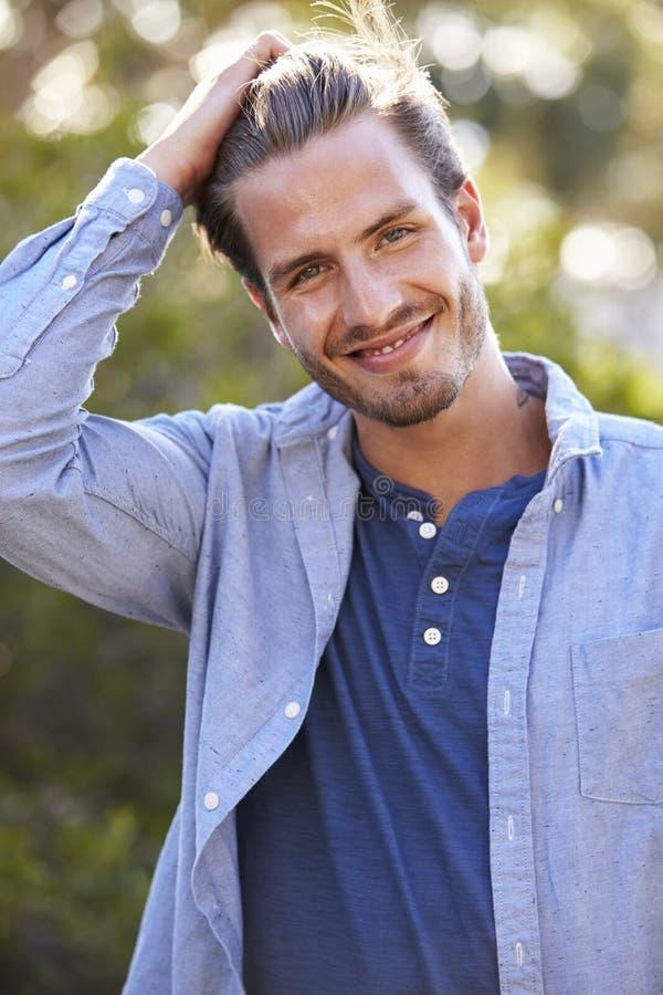 Porträt des jungen weißen Mannes mit der Hand im Haar draußen lizenzfreie stockbilder
